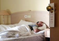 Do not disturb!. The man has a rest in a hotel bedroom Royalty Free Stock Image