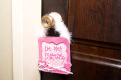 Do Not Disturb. Brown door with a pink Do Not Disturb sign on royalty free stock image