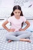Do not disturb child before sleep. Girl child sit on bed in her bedroom. Kid unhappy someone entered her bedroom. Bothering her. Girl kid long hair cute pajamas Stock Photos