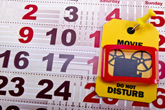 Do not disturb when movie runs. Concept shot. Do not disturb yellow label/tag on a paper calendar background stock photo