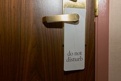 Do Not Disturb sign on a hotel door. Do Not Disturb sign hanging on the handle on a wooden hotel door in a close up view royalty free stock photography