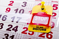 Do not disturb stop sign. Do not disturb at weekend concept shot. Do not disturb yellow label/tag with a stop road sign on a paper calendar background stock photos
