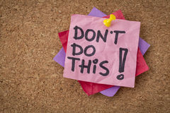 Do not do this advice. Do not do this  advice or warning - handwriting on pink sticky note Royalty Free Stock Images