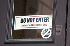 Do not enter. Old door with two signs, no smaoking and do not enter authorized personnel only Stock Photography