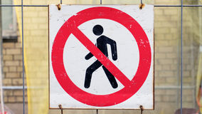 Do not enter sign. With a crossed out figure crosses out on a fence at a construction site Royalty Free Stock Images