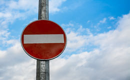 Do Not Enter Street Sign. Represented by a red metal plate with a white thick horizontal line in the center. Blue sky in the background. The metallic plate is Royalty Free Stock Photography