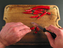 Do not ever lick your fingers after this!. Red peppers on wood with knife and hands cutting Royalty Free Stock Photo