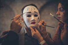 Do not fall under the influence of others. Businesspeople paint a mask on a woman. Close up royalty free stock photography