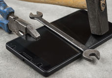 Do not fix your mobile phone with hammer pair of players or an wrench. Do not fix your mobile phone or cell  with hammer pair of players or an wrench Stock Images