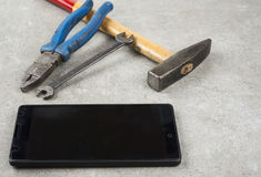 Do not fix your mobile phone with hammer pair of players or an wrench. Do not fix your mobile phone with the hammer pair of players or an wrench Royalty Free Stock Image