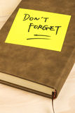 Do not forget note and a notebook. Close up of a post-it note saying do not forget and a notebook on wooden background Stock Photos