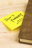 Do not forget note and a notebook. Close up of a post-it note saying do not forget and a notebook on wooden background Royalty Free Stock Images