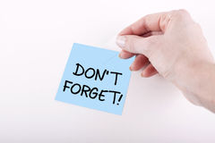 DO NOT FORGET. Woman hand taping DON'T FORGET! note on white surface Royalty Free Stock Photo