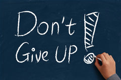 Do not give up. On blue chalkboard with the hand of businessman Stock Images