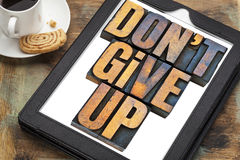 Do not give up phrase on tablet. Do not give up - motivation concept - a phrase in vintage letterpress wood type printing blocks on a digital tablet with a cup stock photos