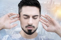 Serious bearded male trying to concentrate. Do not hear. Handsome man keeping eyes closed and touching ears while standing against urban surroundings Royalty Free Stock Photos