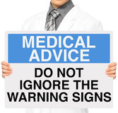 Do Not Ignore Warning Signs. A doctor holding a sign with a medical advice Royalty Free Stock Images