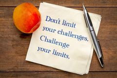 Do not limit your challenges. Challenge your limits. Inspirational handwriting on napkin with a fresh apricot royalty free stock image