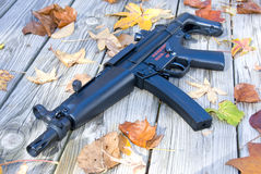 Do not mess with me. Picture of a sub machine gun surrounded by leaves Royalty Free Stock Image