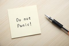 Do not panic. A yellow sticky note is written something on the desk with a ball pen aside Stock Photos