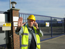Do not pass 2. A work site gate supervisor wearing hige visability vest and yellow hard hat raises his hand to stop visitors while using his mobile phone to get Stock Photography