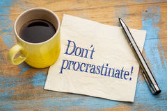 Do not procrastinate reminder note. Do not procrastinate reminder - handwriting on a napkin with a cup of coffee Royalty Free Stock Photos