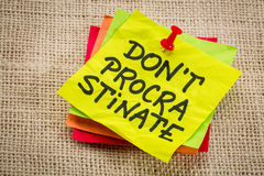 Do not procrastinate reminder note. Do not procrastinate reminder on a yellow sticky note Royalty Free Stock Images