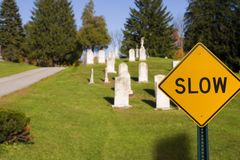 Do not rush. Slow road sign near cemetery: what does it mean royalty free stock photography