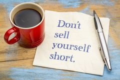 Do not sell yourself short. Inspirational handwriting on a napkin with a cup of coffee royalty free stock image