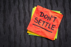 Do not settle reminder on sticky note. Do not settle - motivational advice or reminder on a sticky note against black lokta paper Royalty Free Stock Photo