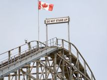 Do not stand up warning on top of roller coaster. Top of a wooden roller coaster set against a clean blue sky. The Canadian flag and a Do Not Stand Up! warning Stock Images