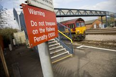 Do not trespass on the railway. In the foreground, a sign saying Warning - Do not trespass on the Railway - Penalty £1000.  In the background, a railway track Royalty Free Stock Image
