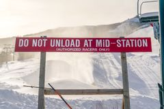 Do Not Unload At Mid Station sign in Park City. Do Not Unload At Mid Station sign against snow covered mountain, ski lifts, and sky at a ski resort in Park stock photos