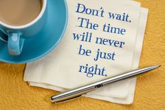 Do not wait. The time will never be just right. Handwriting on a napkin with a cup of coffee against colorful textured paper royalty free stock images