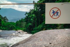 Do not walk of the trail. Warning sign in national park at waterfall in green tropical forest and mountain. Warning sign stock photos