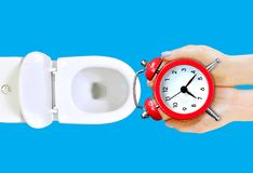 Do not waste your time advice.  The girl is going to throw the alarm clock in the toilet. Wasting time concept. stock photography