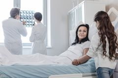 Worried daughter visiting her positive minded mom in hospital. Do not worry honey. Cheerful mature lady smiling while lying in a hospital bed and talking to her Stock Photos