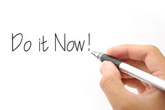 Do it Now!. Do it now concept with hand holding pen against white background Royalty Free Stock Image
