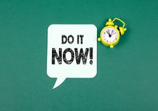 Do it now concept. Paper speech bubble and Alarm Clock on a Green Background stock image