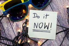 Do it now A conceptual handwritten message on the white paper with wooden background and two sunglasses of different colors with l. Do it now Conceptual royalty free stock image