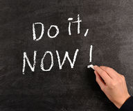 Do it, NOW !. Hand writing Do it , Now! with chalk on a blackboard Royalty Free Stock Photography