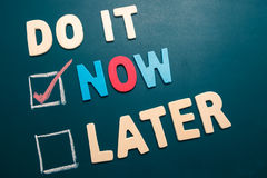 Do It Now or Later with checkbox and red check on blackboard. Time management concept - business concept - Do It Now or Later with checkbox and red marking on Royalty Free Stock Images