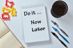 Do it now not later text on notepad with office accessories. Business motivation, inspiration concepts stock image