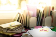 Do Now; Stack of Documents. Working or Studying at messy desk. Royalty Free Stock Image