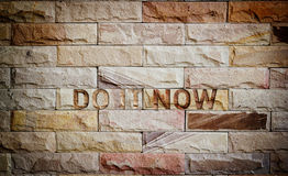 Do it now text on brown brick wall, business concept. Do it now text on brick wall, business concept Stock Images