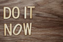 Do It Now on wooden background business concept royalty free stock photography