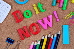 Do it NOW words. On cork background Royalty Free Stock Photography