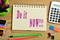 Do it now!. Do it now written on notebook Stock Photography