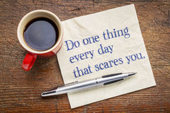 Do one thing every day that scares you - napkin concept. Do one thing every day that scares you - motivational text on a napkin with a cup of coffee stock photo