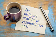 Do ordinary things in an extraordinary way. Motivational handwriting on a napkin with a cup of espresso coffee Stock Photos